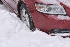 L'automobile con l'inverno si stanca sulla strada innevata Fotografie Stock