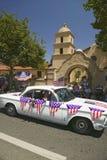 L'automobile décorée de fête de vintage fait sa rue principale de manière vers le bas pendant un quatrième de défilé de juillet d Image libre de droits