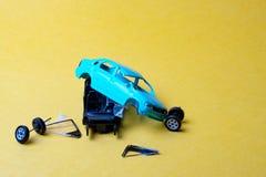 L'automobile del giocattolo tagliata nei pezzi, nelle ruote e nel vetro ha cad da immagini stock