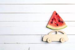 L'automobile di legno del giocattolo con la fetta di anguria sul tetto su bianco corteggia immagine stock libera da diritti