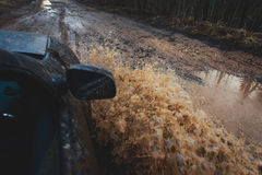 L'automobile di Suv 4wd guida attraverso la pozza fangosa, strada fuori strada della pista, con una grande spruzzata, durante la  Immagini Stock