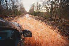 L'automobile di Suv 4wd guida attraverso la pozza fangosa, strada fuori strada della pista, con una grande spruzzata, durante la  Fotografia Stock Libera da Diritti