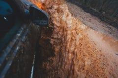 L'automobile di Suv 4wd guida attraverso la pozza fangosa, strada fuori strada della pista, con una grande spruzzata, durante la  Fotografie Stock Libere da Diritti