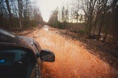 L'automobile di Suv 4wd guida attraverso la pozza fangosa, strada fuori strada della pista, con una grande spruzzata, durante la  Fotografie Stock
