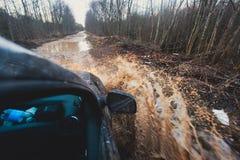 L'automobile di Suv 4wd guida attraverso la pozza fangosa, strada fuori strada della pista, con una grande spruzzata, durante la  Immagine Stock Libera da Diritti