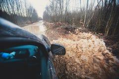 L'automobile di Suv 4wd guida attraverso la pozza fangosa, strada fuori strada della pista, con una grande spruzzata, durante la  Fotografia Stock