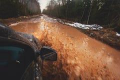 L'automobile di Suv 4wd guida attraverso la pozza fangosa, strada fuori strada della pista, con una grande spruzzata, durante la  Immagine Stock