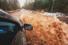 L'automobile di Suv 4wd guida attraverso la pozza fangosa, strada fuori strada della pista, con una grande spruzzata, durante la  Immagini Stock Libere da Diritti