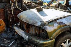L'automobile dopo il fuoco Automobile fuori bruciata con un cappuccio aperto Il motore brucia Immagine Stock Libera da Diritti