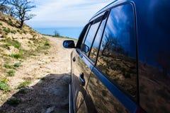 l'automobile fuori strada si muove lungo una strada della montagna della sporcizia fotografie stock