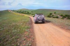 l'automobile fuori strada si muove lungo una strada della montagna della sporcizia immagine stock