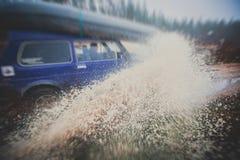 L'automobile fuori strada 4wd di Suv guida attraverso la pozza fangosa, strada fuori strada della pista, con una grande spruzzata Fotografie Stock Libere da Diritti