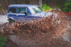L'automobile fuori strada 4wd di Suv guida attraverso la pozza fangosa, strada fuori strada della pista, con una grande spruzzata Fotografie Stock