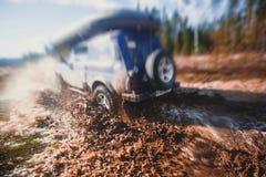 L'automobile fuori strada 4wd di Suv guida attraverso la pozza fangosa, strada fuori strada della pista, con una grande spruzzata Immagini Stock