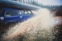 L'automobile fuori strada 4wd di Suv guida attraverso la pozza fangosa, strada fuori strada della pista, con una grande spruzzata Immagine Stock Libera da Diritti