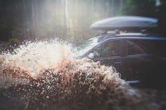 L'automobile fuori strada 4wd di Suv guida attraverso la pozza fangosa, strada fuori strada della pista, con una grande spruzzata Fotografia Stock