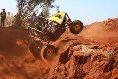 L'automobile gialla che dilaga dal riparo ripido, ruote anteriori ha sospeso, Fotografie Stock Libere da Diritti