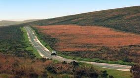 L'automobile guida giù la collina nel paesaggio irregolare video d archivio