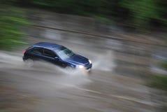 L'automobile guida nella pioggia all'alta velocità Fotografie Stock