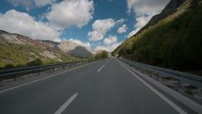 L'automobile guida rapidamente lungo la strada asfaltata in campagna nel giorno di estate all'aperto lungo le montagne archivi video
