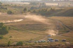 L'automobile guida su un giacimento vuoto della sabbia e su una colonna gialla degli aumenti della polvere fotografia stock libera da diritti