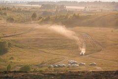 L'automobile guida su un giacimento vuoto della sabbia e su una colonna gialla degli aumenti della polvere immagine stock libera da diritti