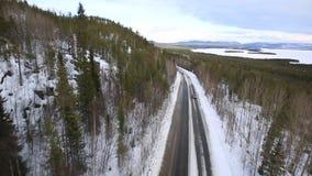 L'automobile guida su una strada dell'inverno fra il legno e stock footage