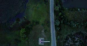 L'automobile guida sulla strada di sera fuori della città Il ponticello sopra il fiume Volo aereo sopra la strada della campagna  video d archivio