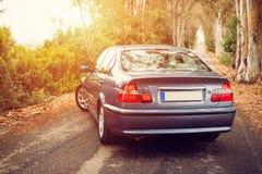 L'automobile ha parcheggiato su una strada della natura con lo spolight arancio del sole nella parte anteriore Fotografia Stock Libera da Diritti