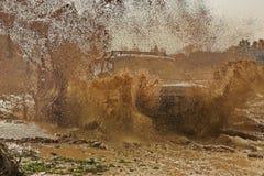 L'automobile ha slittato su una strada bagnata L'automobile crea una grande nuvola della sporcizia e della polvere fuori strada immagine stock