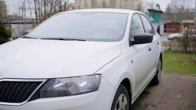 L'automobile moderna bianca è lasciata nella via il giorno nuvoloso grigio di autunno senza gente stock footage