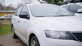 L'automobile moderna bianca è lasciata in via il giorno nuvoloso di autunno senza gente archivi video