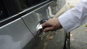 L'automobile pugnalante della mano digita il foro della maniglia e torce per aperto con la mano che alz tirandoare archivi video