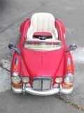 L'automobile rossa d'annata del giocattolo per i bambini ed il bambino nella via, automobile del giocattolo ha parcheggiato sulla Fotografia Stock