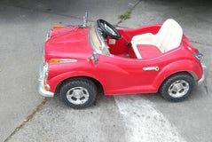 L'automobile rossa d'annata del giocattolo per i bambini ed il bambino nella via, automobile del giocattolo ha parcheggiato sulla Fotografie Stock
