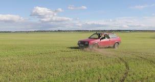 L'automobile rossa guida il campo e fa trucchi archivi video