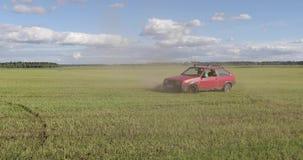 L'automobile rossa guida il campo e fa trucchi stock footage