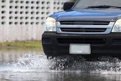 L'automobile spruzza attraverso una grande pozza su una via sommersa Immagini Stock Libere da Diritti