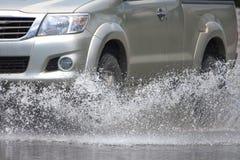 L'automobile spruzza attraverso una grande pozza su una via sommersa Fotografie Stock Libere da Diritti