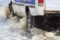 L'automobile spruzza attraverso una grande pozza sull'sommersa Fotografia Stock