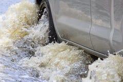 L'automobile spruzza attraverso una grande pozza sull'sommersa Fotografia Stock Libera da Diritti