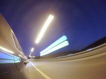 L'automobile sta muovendosi all'alta velocità sulla strada di città di notte Fotografia Stock