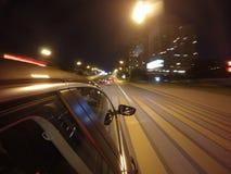 L'automobile sta muovendosi all'alta velocità sulla strada di notte nella città Fotografia Stock Libera da Diritti