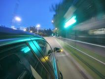 L'automobile sta muovendosi all'alta velocità sulla strada di notte nella città Immagini Stock