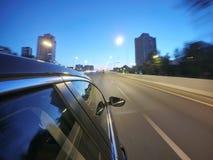 L'automobile sta muovendosi all'alta velocità sulla strada di notte nella città Fotografia Stock