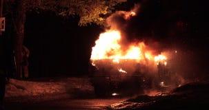 L'automobile su fuoco con un pompiere prepara il tubo flessibile per l'estinzione archivi video