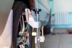 L'automobile sul supporto con i sensori sulle ruote per la curvatura di allineamento di ruote controlla l'officina del distributo Fotografie Stock Libere da Diritti