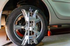 L'automobile sul supporto con i sensori sulle ruote per la curvatura di allineamento di ruote controlla l'officina del distributo Immagini Stock Libere da Diritti
