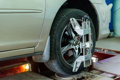 L'automobile sul supporto con i sensori sulle ruote per la curvatura di allineamento di ruote controlla l'officina del distributo Fotografia Stock Libera da Diritti