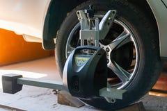 L'automobile sul supporto con i sensori sulle ruote per la curvatura di allineamento di ruote controlla l'officina del distributo Immagine Stock